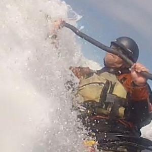 paddler surfing with Blue Dog Kayaking